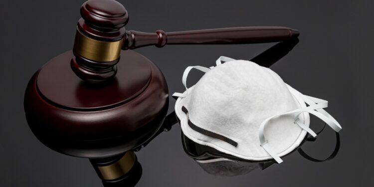 Ein Richterhammer und ein Mundschutz auf schwarzem Hintergrund