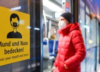 Ein Mann mit Schutzmaske steigt in eine Bahn ein.