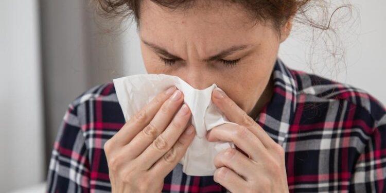 Eine Frau putzt sich die Nase mit einem Taschentuch.