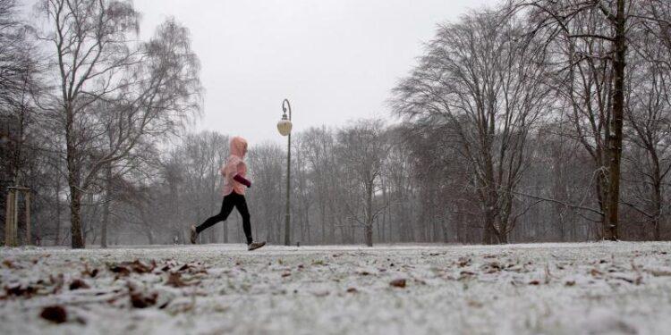 Eine Person joggt im Schnee.