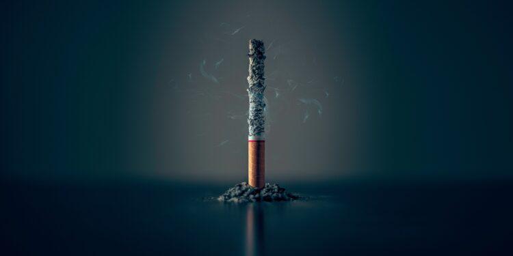 Hochkant stehende Zigarette mit Asche