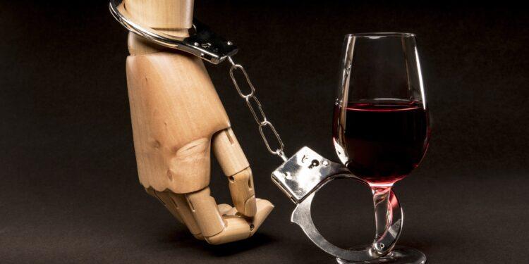 Holzhand ist per Handschelle mit einem Rotweinglas verbunden.