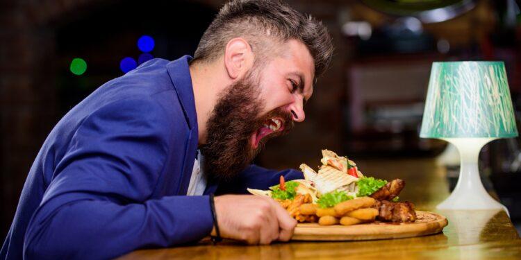 Mann nimmt ein Cheat-Meal zu sich.