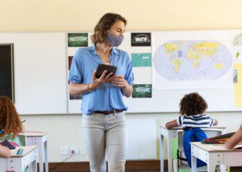 Eine Lehrerin mit Mundschutz unterrichtet eine Schulklasse.