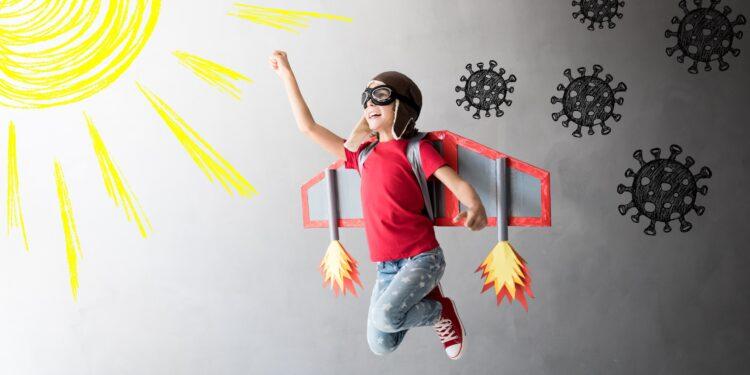 Kind mit Flugzeugflügeln und umkreist von Coronaviren springt einer gezeichneten Sonnen entgegen.