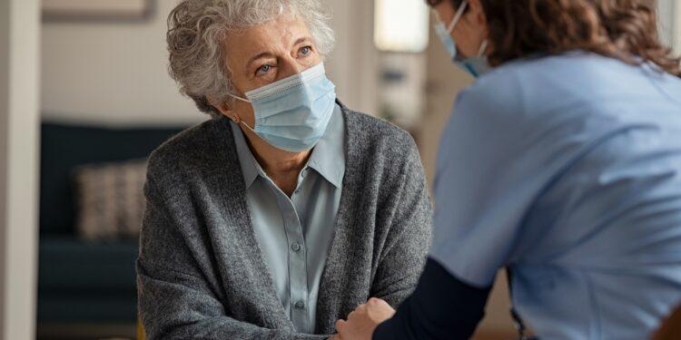 Seniorin mit medizinischer Maske wird zuhause von Ärztin betreut