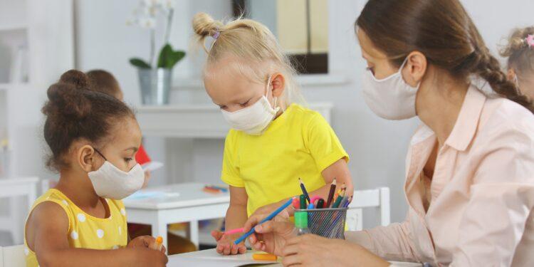 Erzieherin und zwei Kinder mit Mund-Nasen-Bedeckung