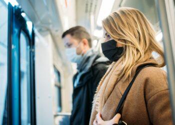 Eine Frau und ein Mann mit Mund-Nasen-Schutz in der U-Bahn