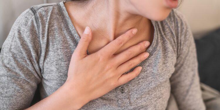 Frau mit Atemproblemen fasst sich an die Brust