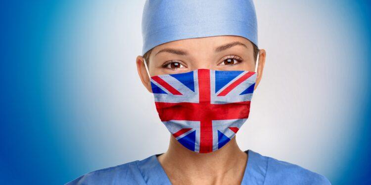 Eine Frau trägt einen Mundschutz, der die Farben der britischen Flagge hat.