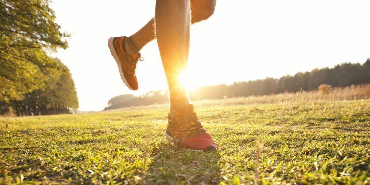 Junger Mann joggt querfeldein auf einer Wiese