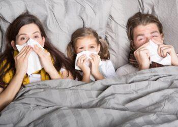Zwei Erwachsene und ein Kind liegen im Bett und putzen sich mit einem Taschentuch die Nase.