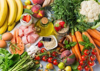Eine Auswahl an verschiedenen - vorwiegend pflanzlichen - Lebensmitteln mit einem Schild mit der Aufschrift DASH-Diet auf einem Tisch