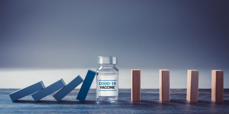 Bauklötze, die sich gegenseitig umschmeißen, werden durch ein Impfstofffläschchen gestoppt.