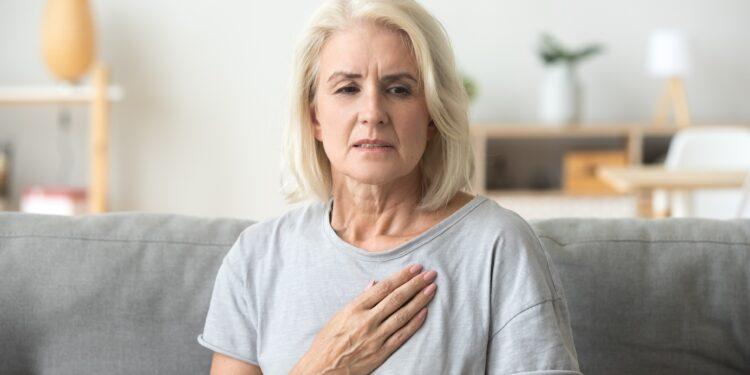 Frau mit Herzschmerzen fasst sich an die Brust