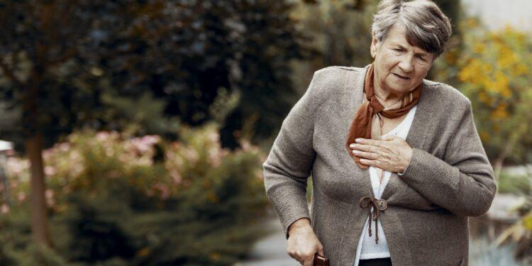 Ältere Frau mit Gehstock fasst sich wegen Atemnot an die Brust