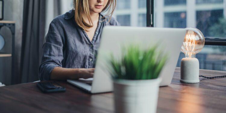 Eine junge Frau arbeitet am Laptop im Homeoffice