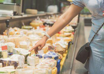 Eine Frau steht vor einer Käsetheke und zeigt auf einen Käse in der Auslage.