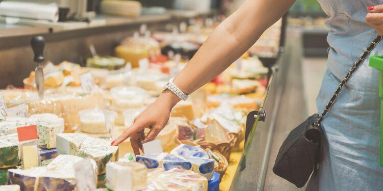 Uma mulher está em frente à mesa de queijos e aponta para uma fatia de queijo na tela.