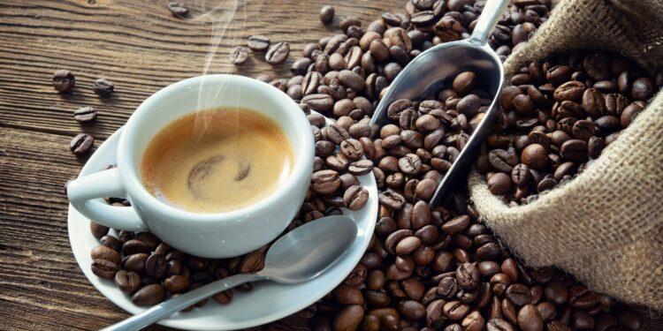 Bild von Kaffee in Tasse zusammen mit Kaffeebohnen.