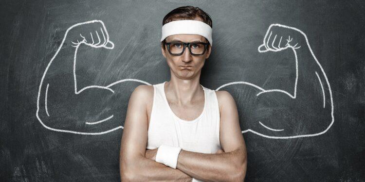 Bild von einem schlanken Mann vor einer Tafel mit aufgemalten Muskeln.