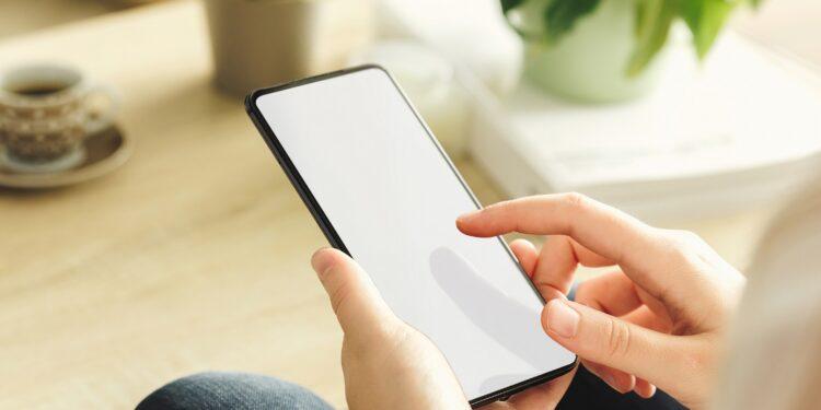 Frau sitzt auf dem Sofa und nutzt ihr Smartphone