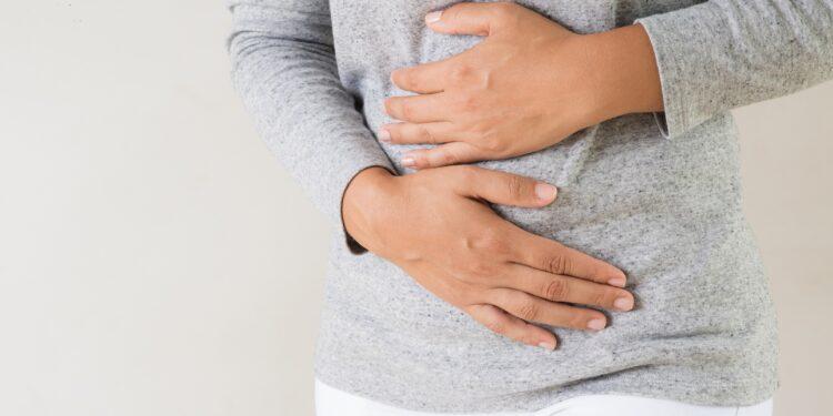 Junge Frau hält sich ihren schmerzenden Bauch