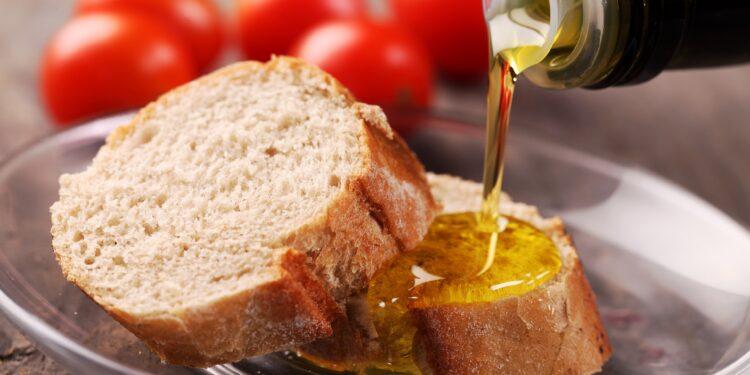 Brotscheiben, auf die Öl gegossen wird, vor frischen Tomaten