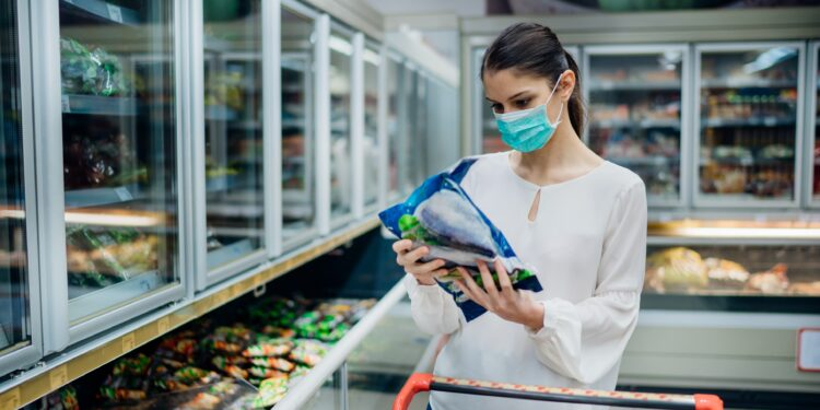 Frau mit OP-Maske liest Beschreibung eines Tiefkühlprodukts im Supermarkt