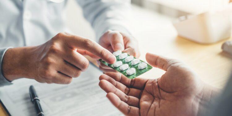 Ein Arzt reicht eine Packung Tabletten an einen Patienten.