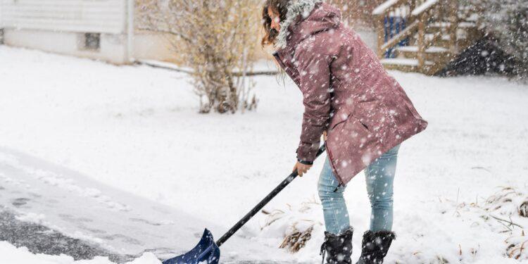 Junge Frau beim Schneeschippen
