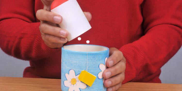 Mann gibt Süßstoff in eine Tasse Tee