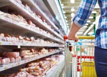 Eine Person schiebt einen Einkaufswagen entlang eines Wurstregals im Supermarkt.