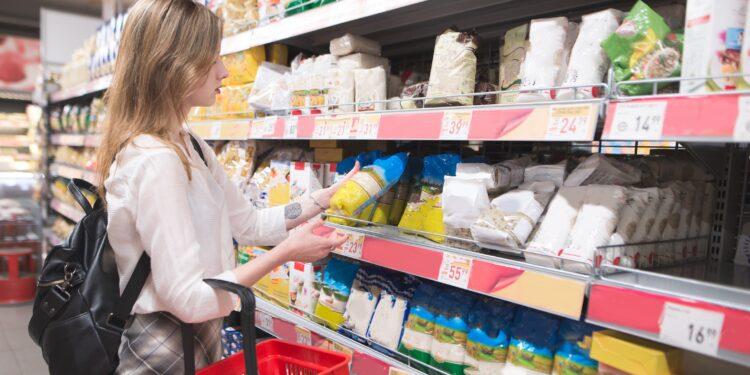 Eine Frau nimmt eine Packung Reis aus einem Regal im Supermarkt.