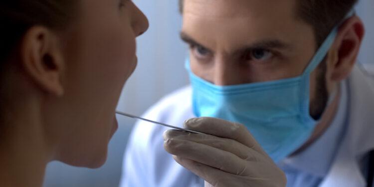 Arzt untersucht den Mundraum einer Patientin