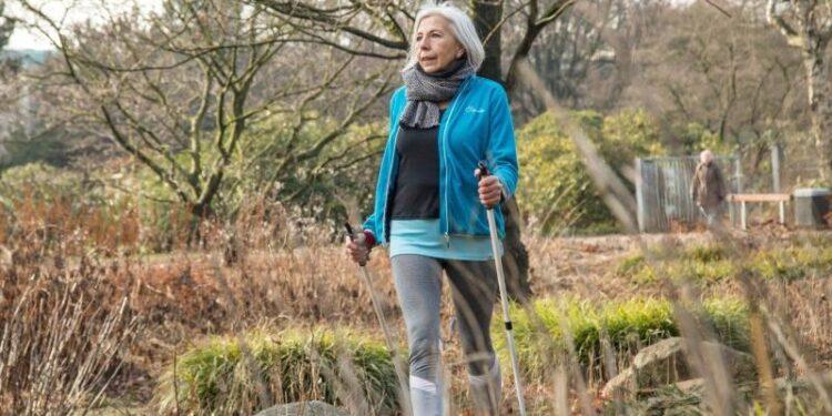 Eine ältere Frau geht in der Natur spazieren.