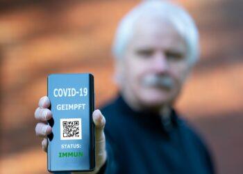 Mann zeigt seinen digitalen Impfpass.