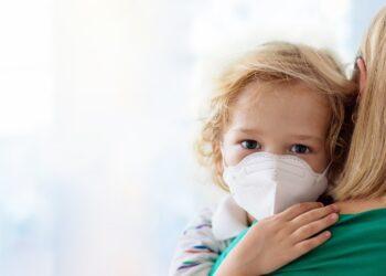 Kind mit Atemschutzmaske auf dem Arm der Mutter.