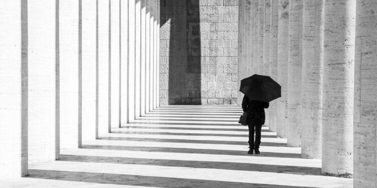 Mann in Schwarz gekleidet mit schwarzem Regenschirm geht einen Gang lang.