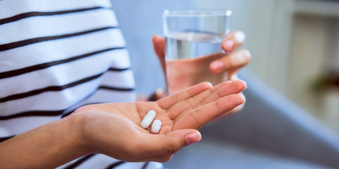 Frau mit zwei Tabletten in der einen und einem Glas Wasser in der anderen Hand