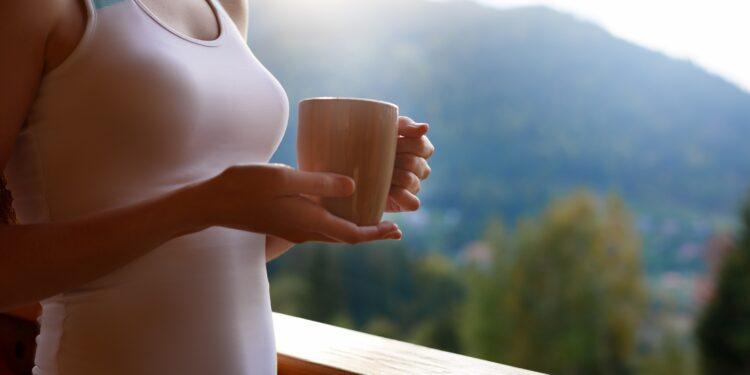 Eine Frau in Sportkleidung trinkt einen Kaffee auf einem Balkon.