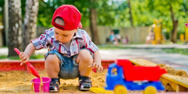 Ein kleiner Junge spielt im Sandkasten.