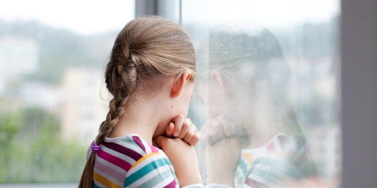 Trauriges Mädchen schaut aus dem Fenster