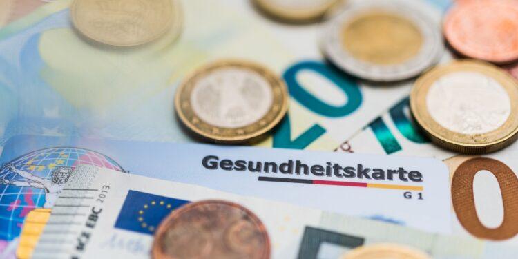Eine Krankenkassenkarte liegt zwischen einigen Geldscheinen und Münzen.