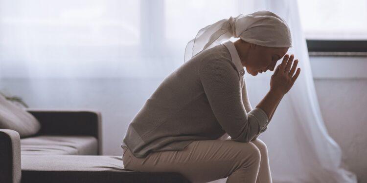 Eine Frau mit einem Tuch auf dem Kopf sitzt in niedergeschlagener Körperhaltung auf dem Sofa.