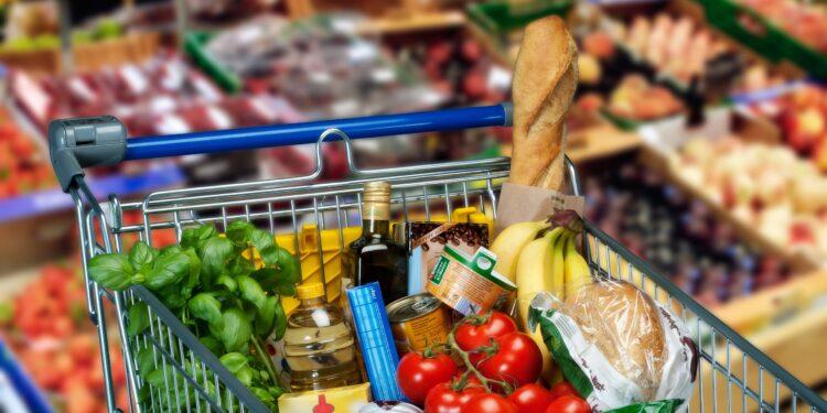 Ein Einkaufswagen gefüllt mit Lebensmitteln steht in einem Supermarkt.