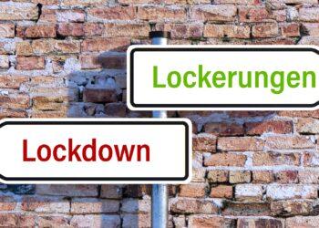"""Zwei Straßenschilder: eins hat die Aufschrift """"Lockdown"""", das andere die Aufschrift """"Lockerungen""""."""