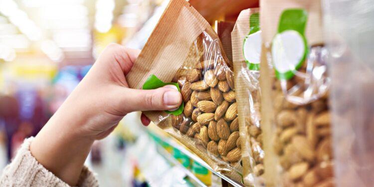 Eine Hand greift nach einer Packung Mandeln aus einem Regal im Supermarkt.