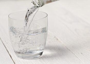 Ein Glas Mineralwasser steht auf einer weißen Oberfläche.