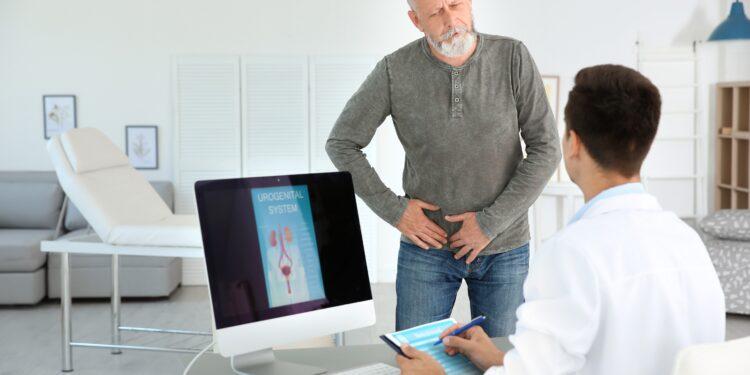Eine Mann spricht mit einem Arzt und drückt dabei auf seinen Lendenbereich.